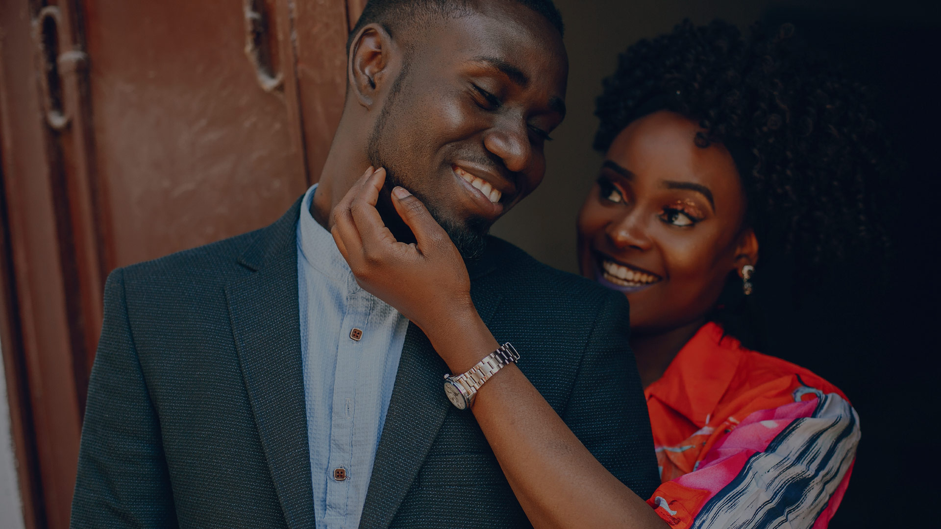 A young and stylish dark-skinned couple standing in a sunny city