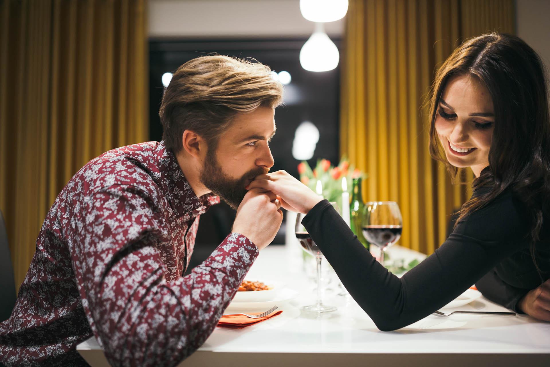 Mann flirtet und küsst Mädchenhand im Café